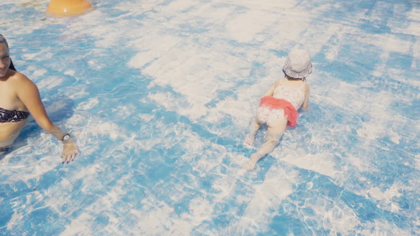 Mother sits in swimming pool while her little daughter in swimsuit crawling | Shutterstock HD Video #22965718