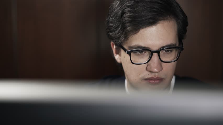 Front view of a young handsome in glasses browsing the Internet at old stylish library. Real time locked down shot.  | Shutterstock HD Video #22968550