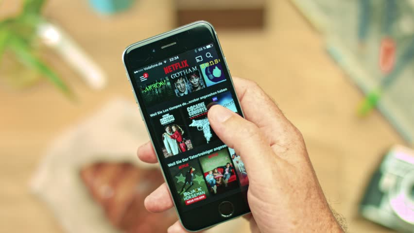 AACHEN, GERMANY - August 2016 : Netflix app on Apple iPhone 6s. Young man is browsing the movie video library what to watch.    Shutterstock HD Video #22969375
