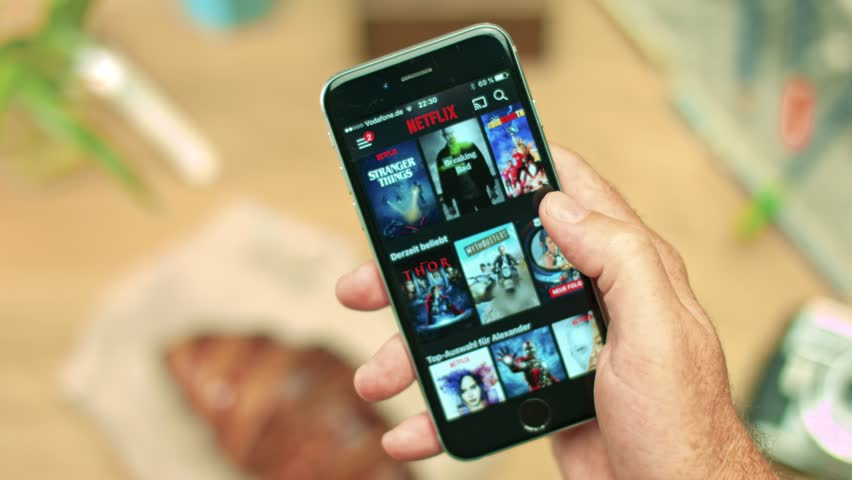 AACHEN, GERMANY - August 2016 : Netflix app on Apple iPhone 6s. Young man is browsing the movie video library what to watch.    Shutterstock HD Video #22969384