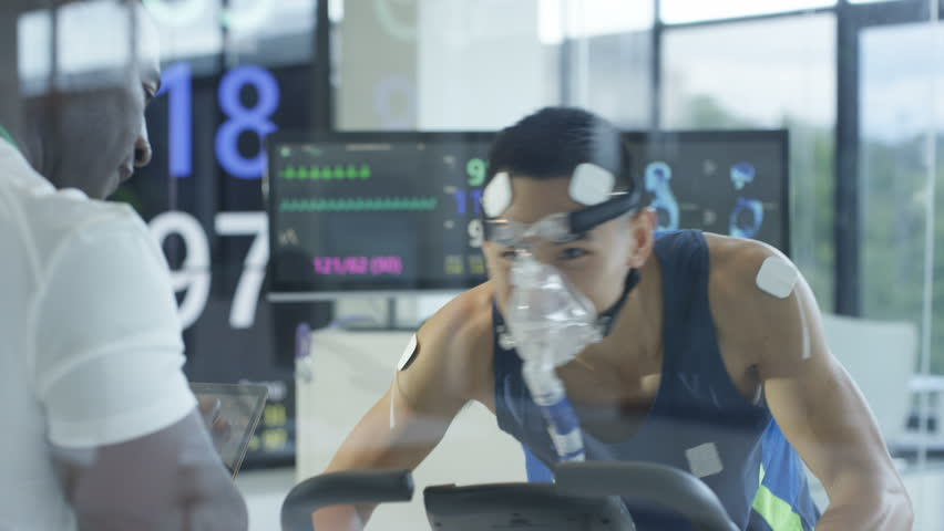 4K Male athlete on exercise bike being tested & monitored by sports scientist Dec 2016-UK | Shutterstock HD Video #22984720