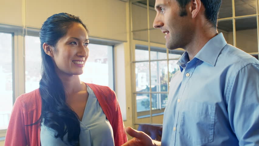 Male and female business executives interacting with each other in office #23008942