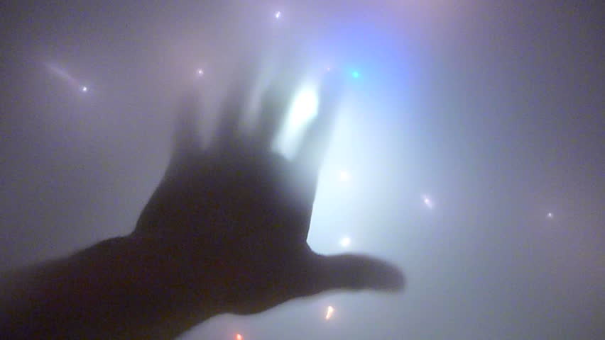 Abstract visual hand and overhead lights appearing to be an alien space craft.