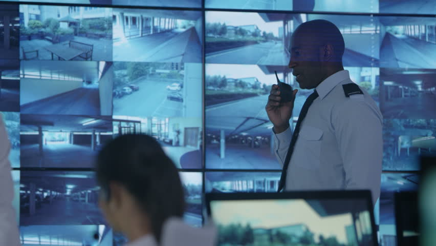 4K Security team watching multiple CCTV video screens in system control room Dec 2016-UK #23015671