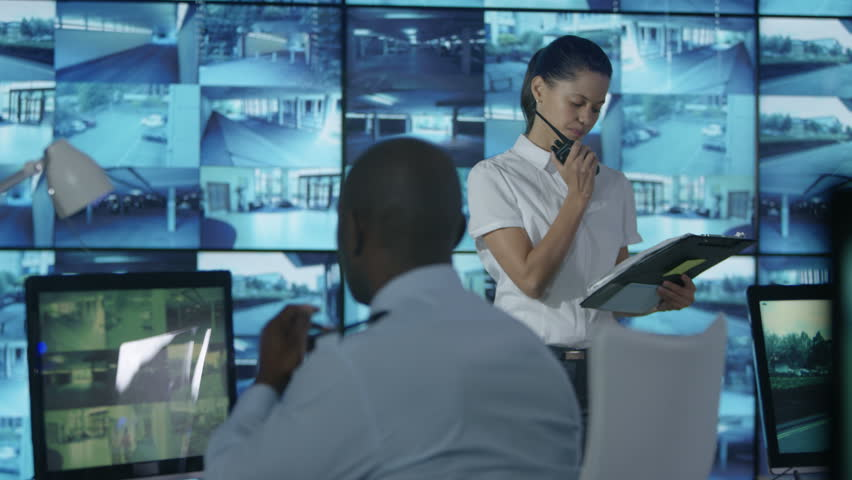 4K Security team watching CCTV screens in control room, officer talking on radio Dec 2016-UK | Shutterstock HD Video #23015761