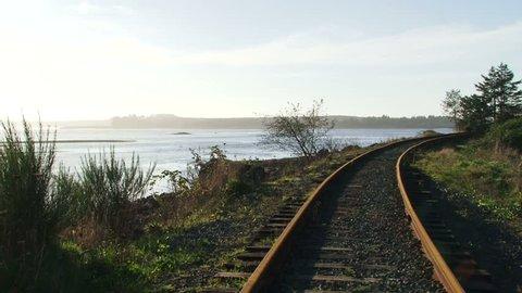 Man balances and walks along railroad tracks near waterway in Oregon.