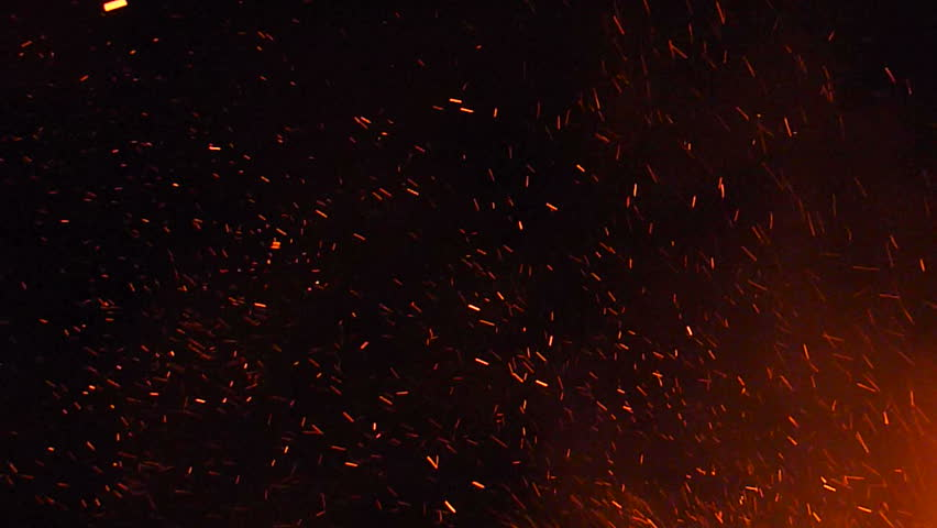 Burning ash rise from large fire in the night sky.