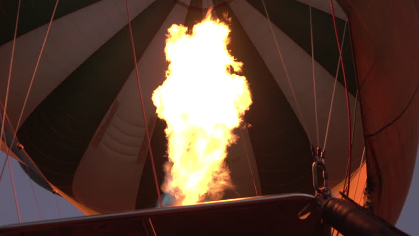 CLOSE UP, POV, LOW ANGLE VIEW: Flight team using burners and gas flame to fill safari balloon with hot air. Inflating colorful baloon and preparing to take off on memorable adventure in Serengeti