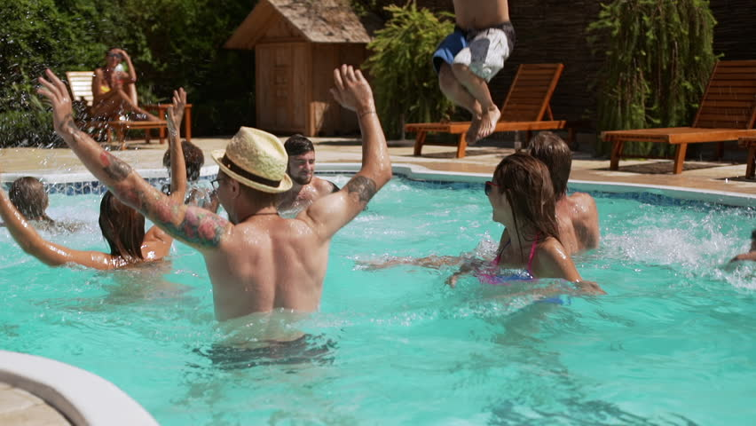 Funny group of friends splashing water in pool with beachball in slowmotion