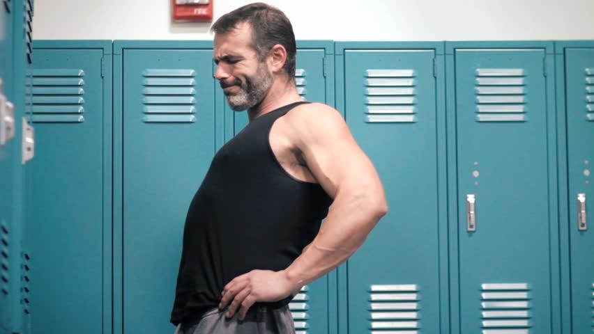 Muscular man in locker room suffers from lower back pain injury