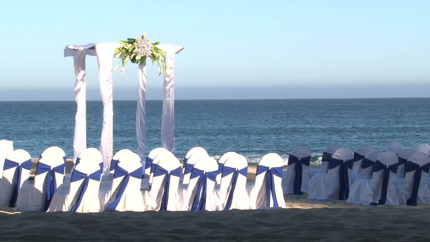 Ocean front wedding ceremony on sandy beach.