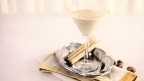 Holiday eggnog cocktail with dark rum and milk garnished with nutmeg.