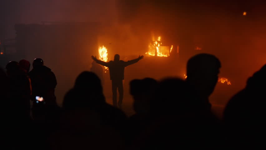 Kiev, Ukraine, January 2014: A protester walks with his hands up near the burning cars during protests against President Yanukovych in Kyiv on the street Grushevskogo January 19, 2014