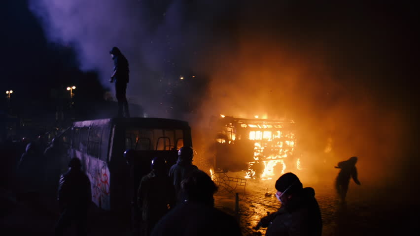 Kiev, Ukraine, January 2014: Protesters against the policy of President Yanukovych throw stones and bang next to a burnt-out machinery in clashes with police on the street Grushevskogo January 19