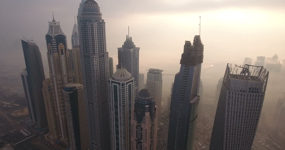 Aerial view of Dubai city at sunrise. Dubai Marina district. Silhouettes of buildings on foggy weather. Aerial view Dubai city skyscrapers, Jumeirah Beach, UAE, Middle East