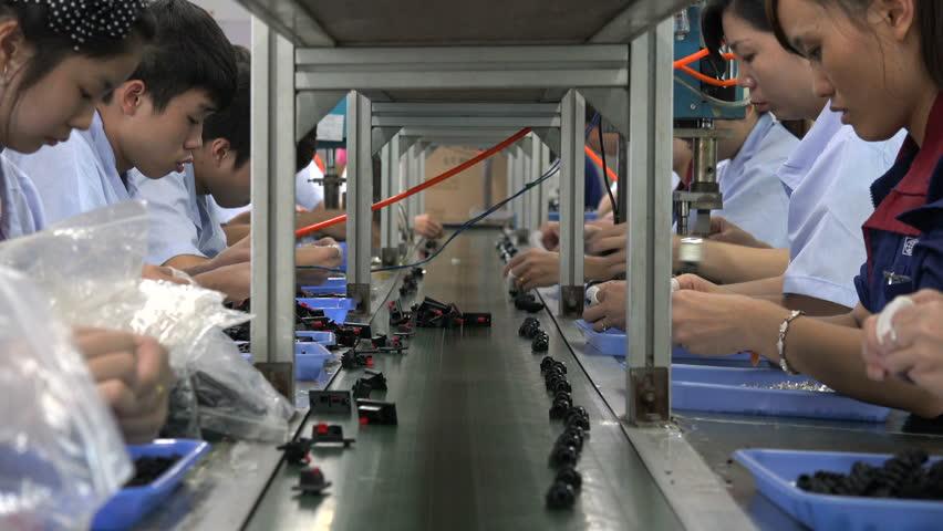 SHENZHEN, CHINA - 16 NOVEMBER 2015: Employees of an electronics factory work on the conveyor belt in Shenzhen, China