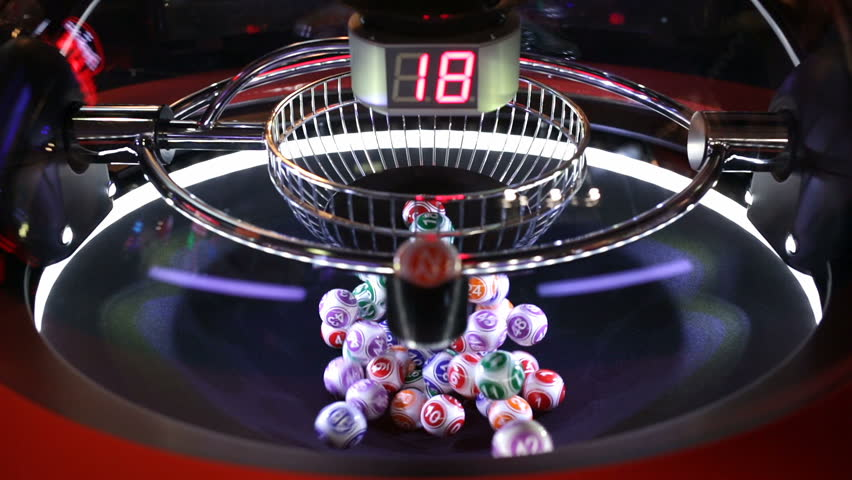 Colourful lottery balls in a rotating bingo machine. Different numbers on a red digital monitor.