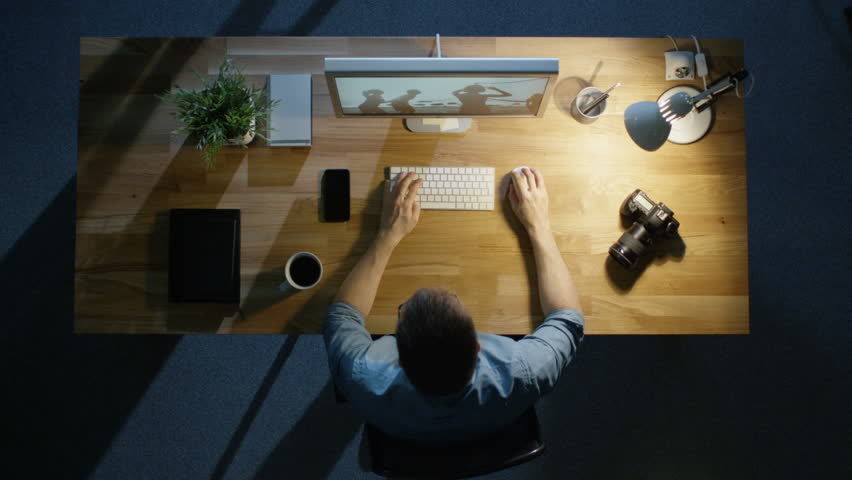 Top View of a Young Photographer Processing Photographs on His Desktop Computer Late at Night. Table Lamp Illuminates His Desk. Camera, External Hard Drive and Notebook Lie Beside Him. | Shutterstock HD Video #23128030