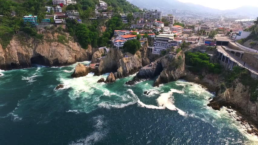 Aerial shot of la Quebrada Guerrero Mexico, the sea, rocks, nature and houses with panoramic view of the city town.
