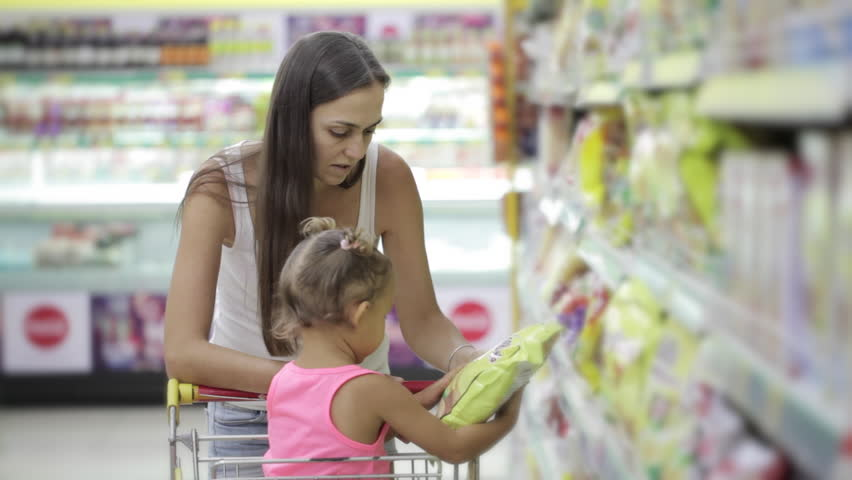 Young attractive mother and little cute daughter selecting a flakes at the supermarket | Shutterstock HD Video #23156386