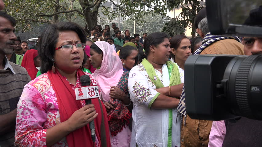 KOLKATA, INDIA - 13 DECEMBER 2014: A female Indian news reporter speaks to the camera during a live broadcast of a protest (against the arrest of a minister) in Kolkata, India
