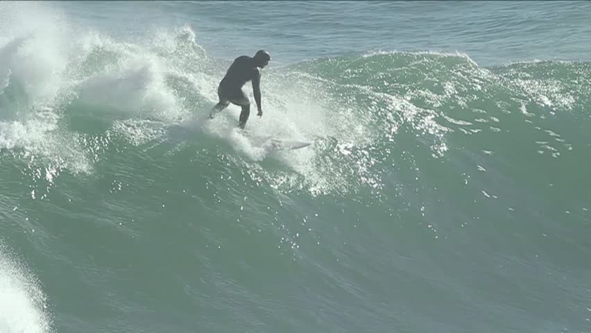 Man surfing as waves crash behind him (slow-motion). Pichilemu, Chile - Feb 2016)   Shutterstock HD Video #23165857