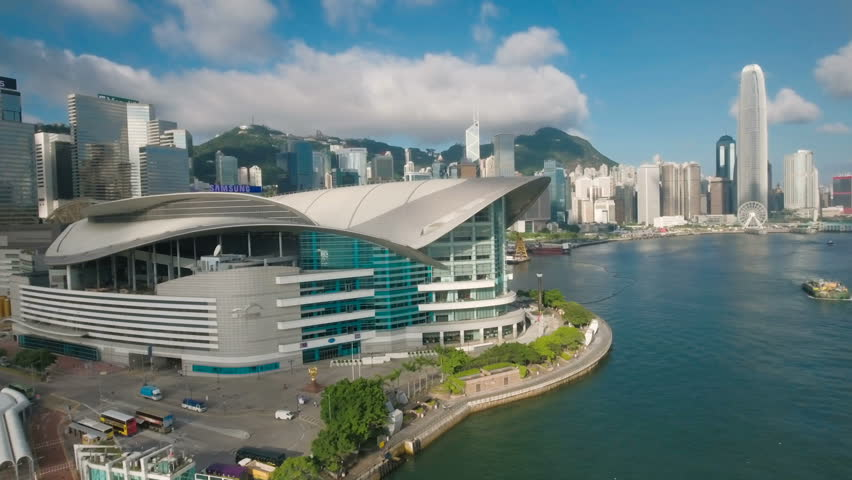 HONG KONG - JULY 2016: Aerial drone shot past the futuristic Expo building reveals the financial and business district and modern skyline of Hong Kong.