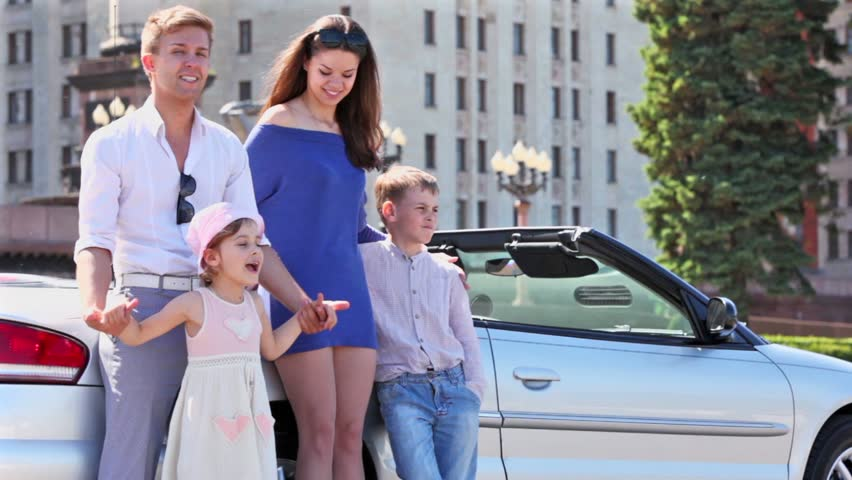 Young couple with two kids stand near cabriolet, boy hold little girl and then embrace his girlfriend, they begin laugh
