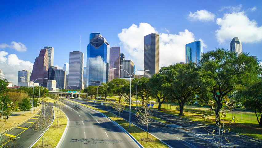 Houston Texas Skyline Clouds Time Lapse 4K 1080p. A time-lapse of Houston cityscape with clouds rolling over buildings and blue skies with traffic from bridge on highway