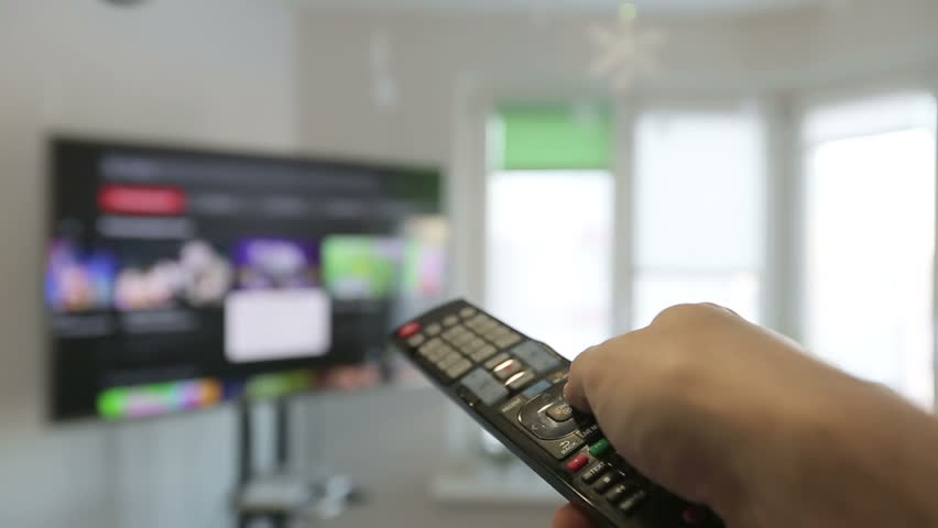 Smart tv and  man hand pressing remote control hanging television channels.  | Shutterstock HD Video #23178688
