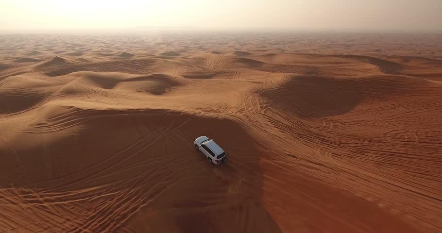 Aerial view of 4x4 off road land vehicle taking tourists on desert dune bashing safari in Dubai, UAE