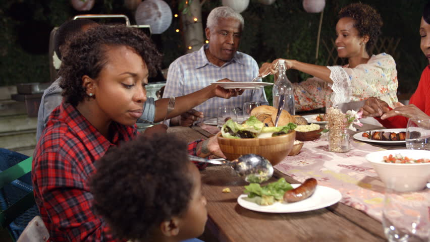 Multi generation black family serving food at table outdoors