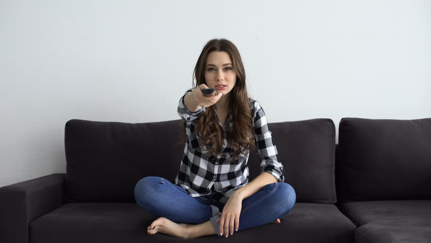 Angry upset woman trying to turn on tv while sitting on a couch at home | Shutterstock HD Video #23198137