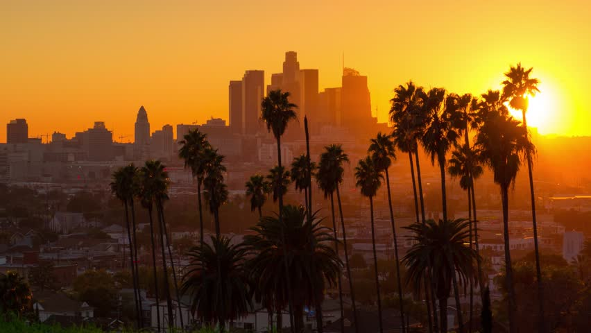 Scenic sunset to night transition zoom out from city of Los Angeles downtown skyline palm trees in foreground. 4K UHD timelapse.