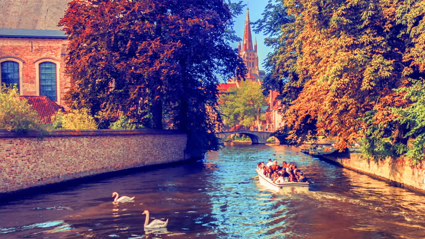 Fall cityscape with tour boats on canal at Begijnhof place. Bruges, Belgium. Panoramic view. . 4K, Ultra High Definition, Ultra HD, UHD, 2160P, 3840 x 2160