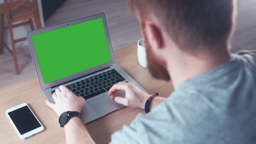 Over the shoulder shot of a young Caucasian man working from home on a laptop, green screen chroma key. 4K UHD 60 FPS slow motion