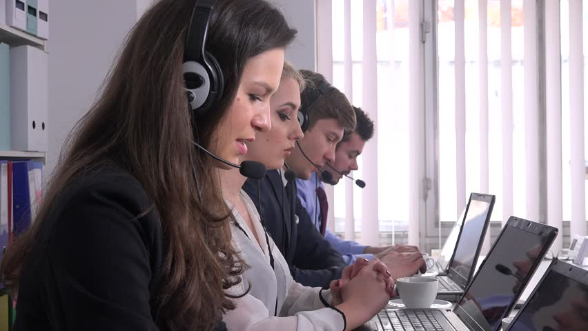 Business people working inside office sales operator call center headsets talk emergency 911 center help needed