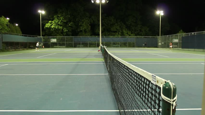 Playing tennis on some beautiful courts at night time.