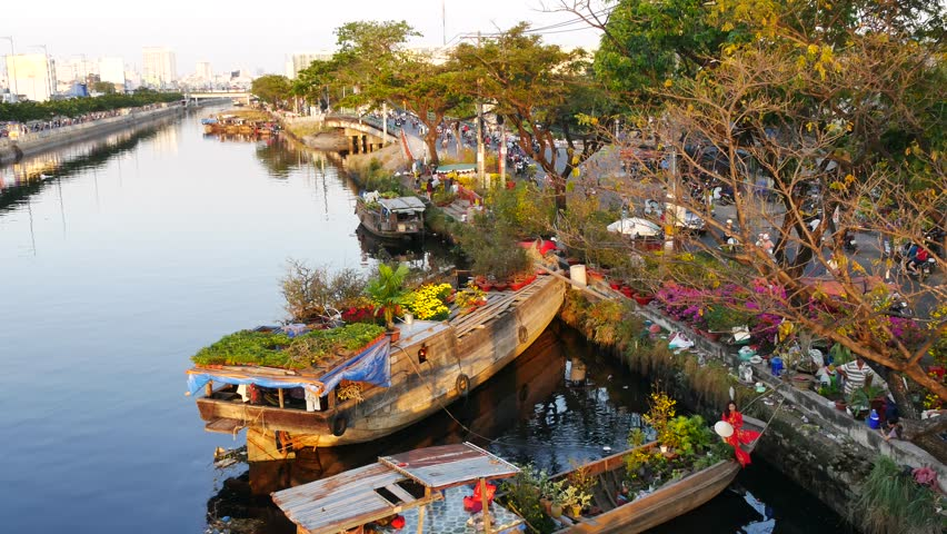Ho Chi Minh city , Vietnam - February 5th, 2016: Boating along canal carry flowers with apricot, confetti, almond tree to sell everyone distillation welcome spring Tet in Ho Chi Minh City, Vietnam
