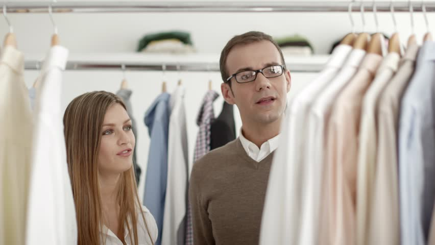 Male customer speaking to sales manager in fashion store while shopping for clothes