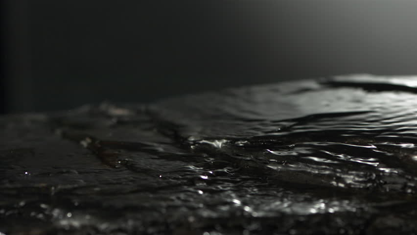 Clear water flow on the surface of the stone. Super slow motion close up