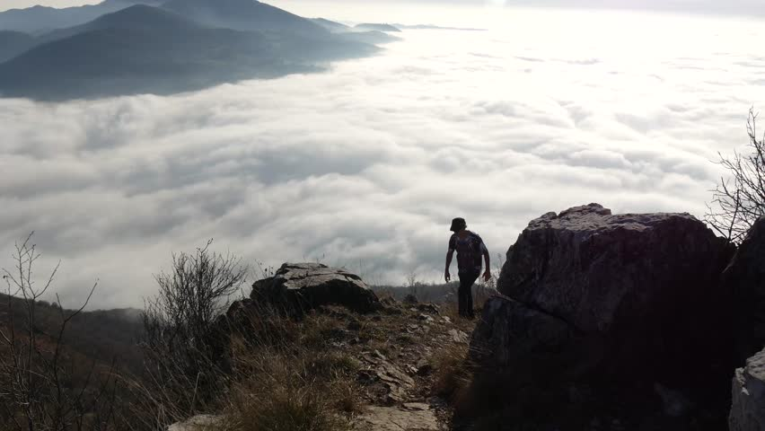 LECCO, ITALY - CIRCA DECEMBER 2016: a hiker walks on a path in the mountains.  An endless sea of clouds cover the plain. | Shutterstock HD Video #23289640