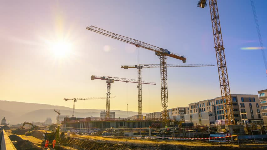 Timelapse footage of a large construction site with several busy cranes, blue sky and the sun