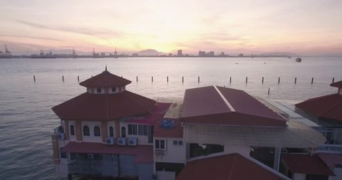 Pullback Reveal Drone Shot of Restaurant and Pier in Penang, Malaysia, at Sunrise
