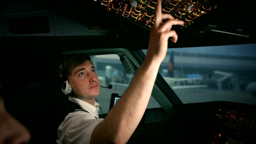 Modern plane or aircraft at the airport runway. The close shot of first pilot's hand. He turns on switches at the overhead control panel . Shot at training center