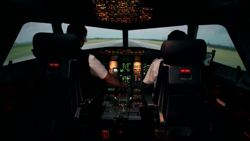 Takeoff of modern passenger aircraft at the international airport. Front view from the cockpit trough windshield. First officer and co-pilot at work during departure the