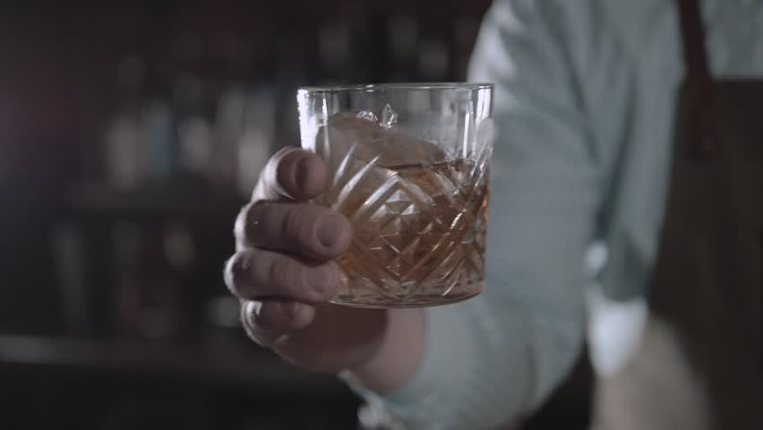Hand holding a glass of whiskey on the rock in bar. Man shake alcohol in bar.