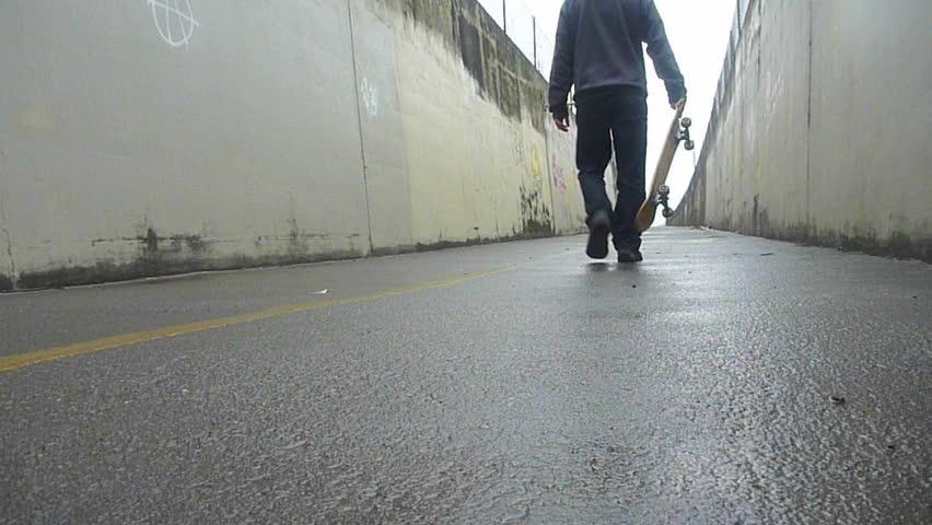 Man walks up concrete, urban path with skateboard.