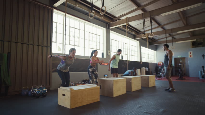 Trainer leading crossfit class on strength training exercise box jumps on wooden crates, intense workout