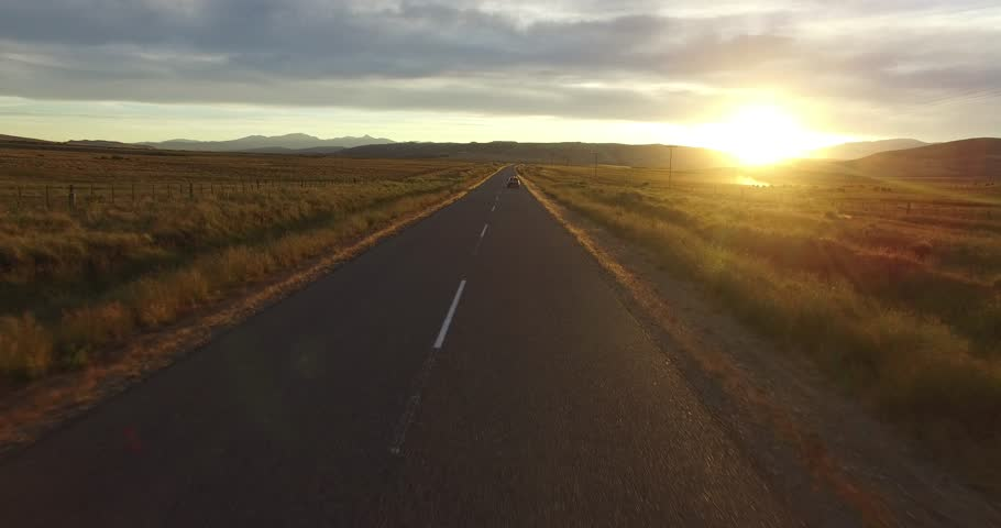Aerial drone scene of route in steppe landscape at sunset golden hour. Camera moving forward following a tracked van on the road.